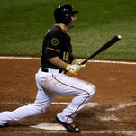 Pittsburgh Pirates' Neil Walker (18) drives in the winning run with a single off  Cincinnati Reds relief pitcher J.J. Hoover during the ninth inning of a baseball game in Pittsburgh Monday, April 21, 2014. The Pirates won 6-5.  (AP Photo/Gene J. Puskar)