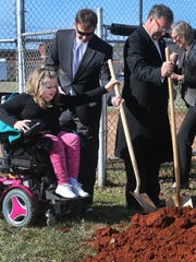 Murfreesboro Councilman Rick LaLance, center, helps Carlee Beam, 8, left, put her shovel away after they broke ground for the Miracle Fields project at McKnight Park, on Thursday, Feb. 4, 2016. Murfreesboro Councilman Eddie Smotherman, right, puts his shovel down after the ceremony.