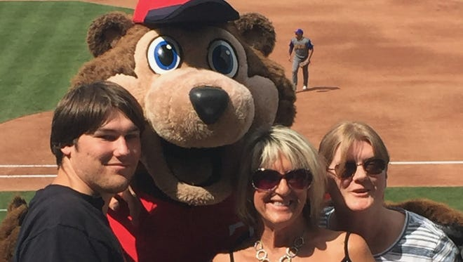 Miles Holtzbach, Shirley Ferrel and Jill Ball pose with T.C., the Twins mascot, at a Twins game as part of a Game Day Bunch, Inc., event.