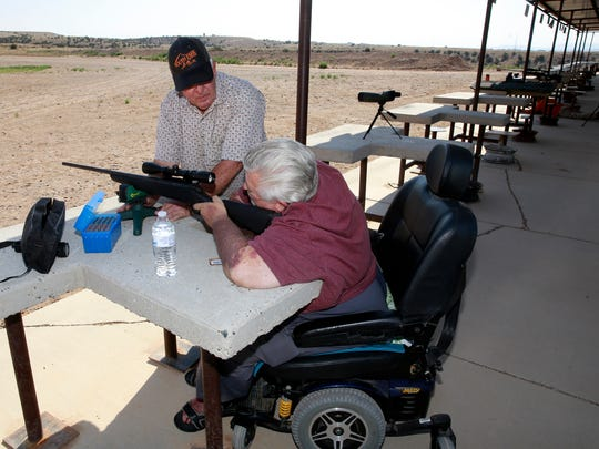 "Carey ""Kirt"" Stidman, of Bloomfield, right, and Craig Hunter sight the scope of Stidman's rifle on June 21 at the San Juan Wildlife Federation shooting range in Farmington."