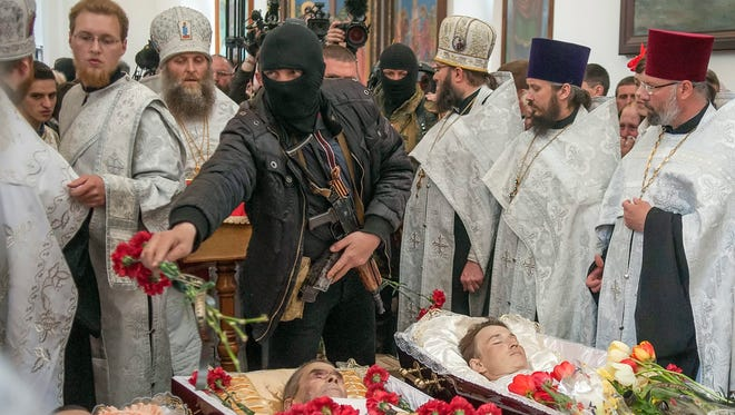 An armed pro-Russian protester attends a funeral ceremony Tuesday for three people killed during a skirmish at a Slaviansk checkpoint, April 19