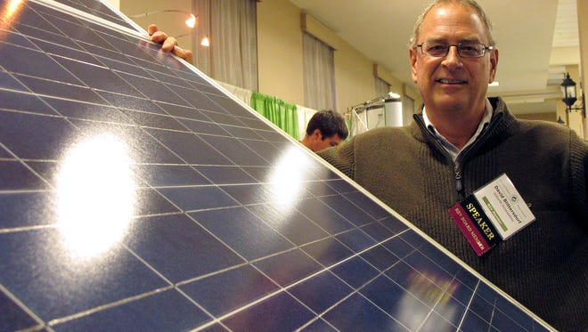David Blittersdorf, president and CEO of Williston-based AllEarth Renewables, stands beside one of his solar trackers at the Renewable Energy Vermont conference and expo in South Burlington in 2013.