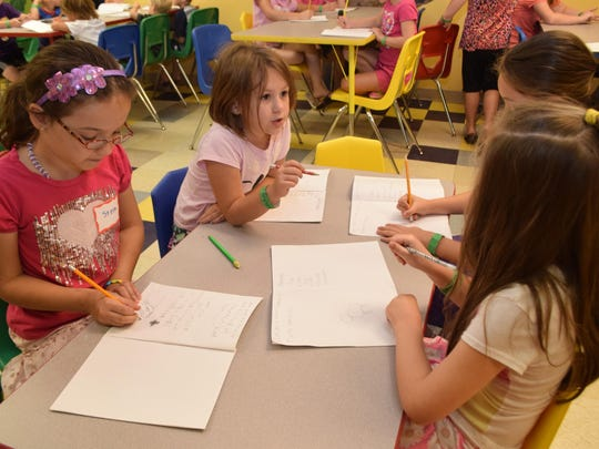 Stella Voorhies (far left,), Alyssa Talley, Arianna Pacchiarotti and Lillian Hilborn write and draw in their journals. Campers in the Get Set to Be A Vet Camp at the T.R.E.E. House Children's Museum are learning this week about how to care for animals.