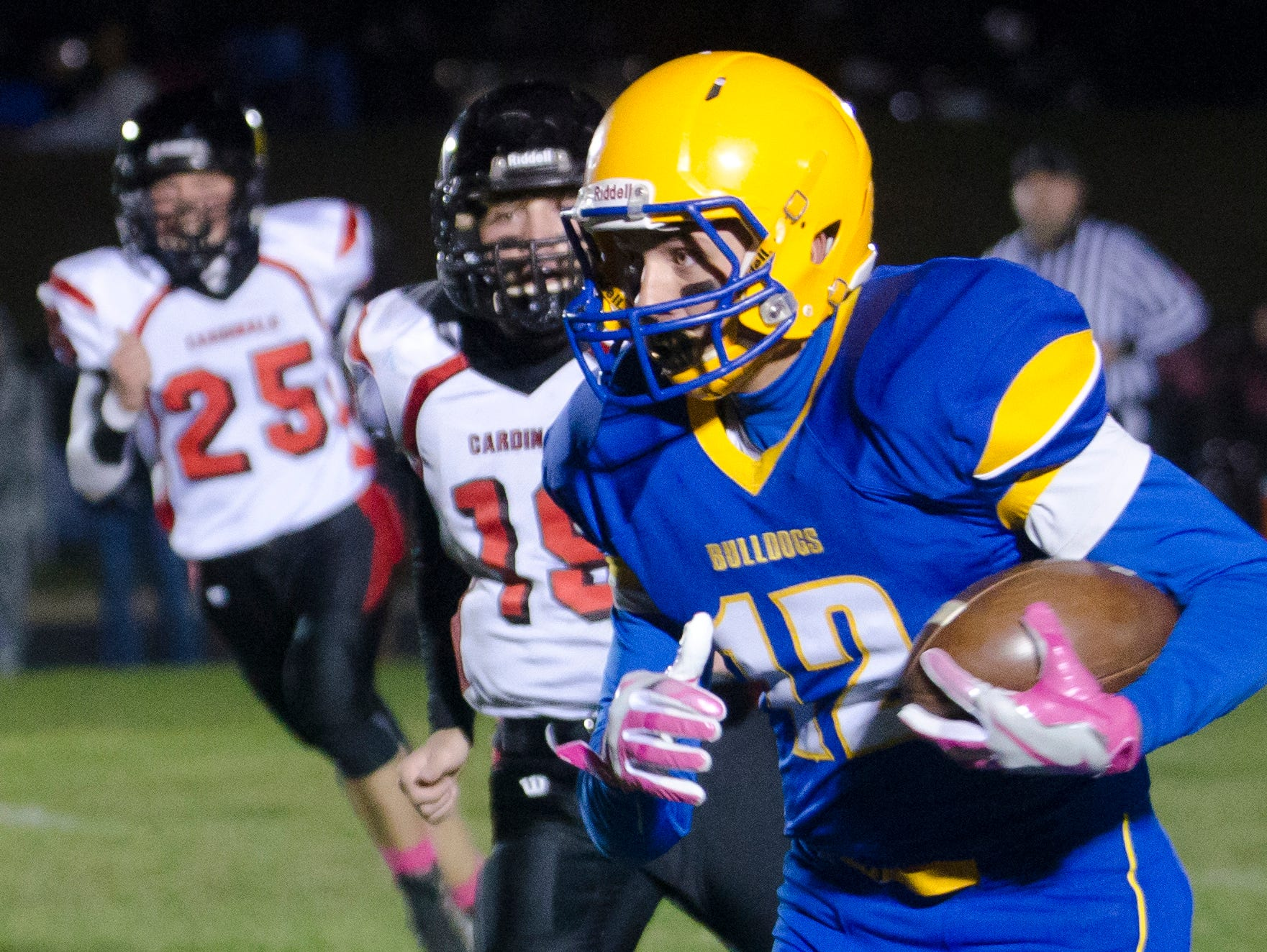 Jon Wilhelmsen of Baltic carries the ball Tuesday, Oct. 25, past Deuel defenders Tanner Troska (19) and Tristen Kwasniewski (25) in the first round of the Class 9AA playoffs at Baltic.
