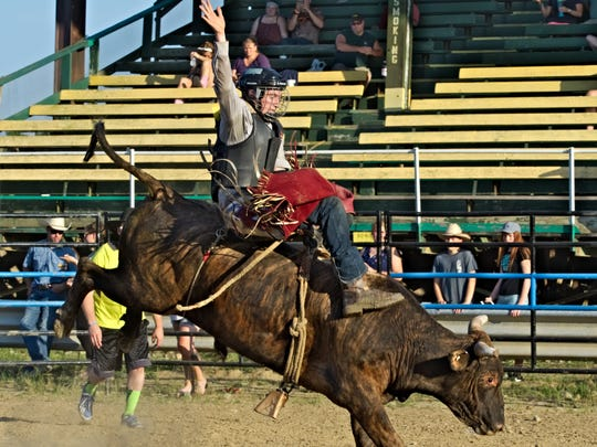 Logan Harter, 15, rides a bull during Lost Nation Rodeo's