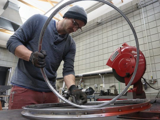 Garrett Arnold cleans up a rim from an old bicycle at one of the art labs at the University of Wisconsin-Marathon County in Wausau, Friday, March 20, 2015.