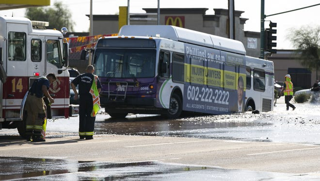 Firefighters look at at a bus sitting in a sinkhole.