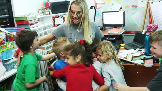 Gulf Elementary School kindergarten teacher Brooke Przespolewski is mobbed by students after winning the Golden Apple on Friday.