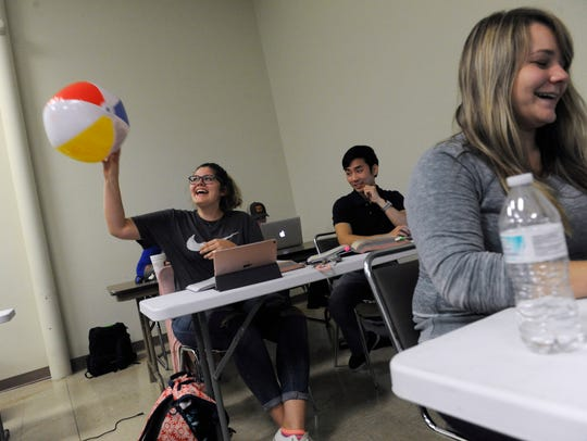 Chelsea Walls,19, tosses a beach ball to the next student
