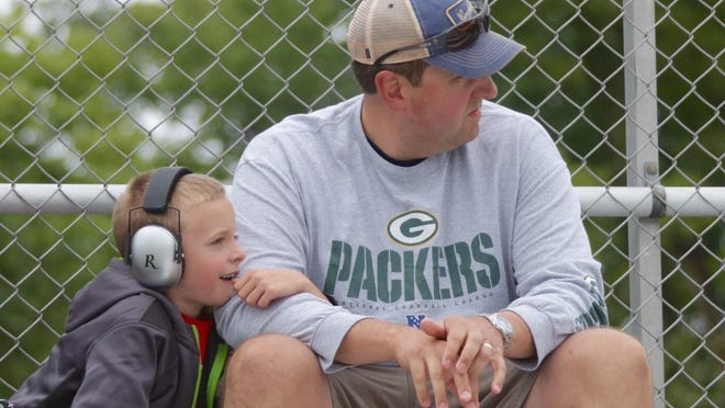 Rick Moser, right, sits on the grandstand with his son Jack, 7, both of Green Bay while watching the Road America 180 Fired up by Johnsonville on Saturday.