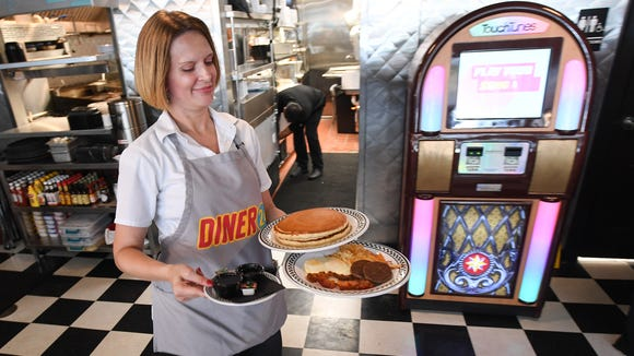 Dinner 24 server Rachel Sanders serves hot cakes at the dinner on Coffee St. in downtown Greenville on Wednesday, July 12, 2017.