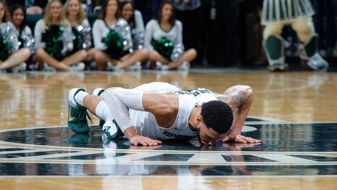 Denzel Valentine kisses the Spartan logo before exiting Saturday's game against Ohio State.