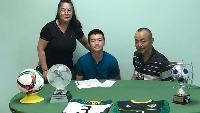 Ryo Suzuki, center, with his mother, Risa Suzuki, left, and father, Makoto Suzuki. Ryo Suzuki was given a partial scholarship after signing to play soccer for the University of Guam Tritons.