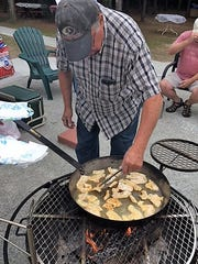 Ron Stahl fries freshly caught fish during a 4-H outing