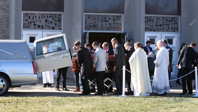 The body of Louisville Metro Council President Jim King is placed in a hearse after a Mass and funeral service at St. Raphael Catholic Church.