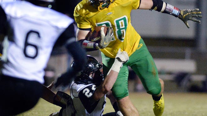Eastern Alamance running back Colby May tries to break free from a Rockingham County defender during a football game last season.