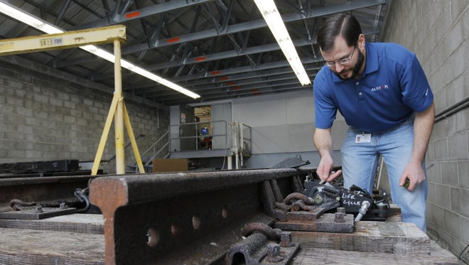 File photo: Development engineer Matthew Romanishan of Rochester, adjusts a 7R switch circuit controller on the test track at Alstom Signaling, hangs cable and assembles a rack in Henrietta in 2011.