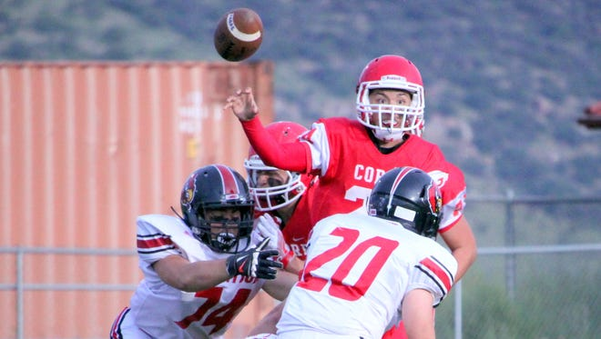 Cobre quarterback Andru Sanchez fires a ball under pressure during football action Friday night against Robertson. He had 177 yards passing on the night.