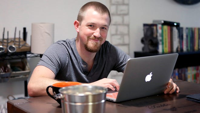 Mitchell Timme works from his laptop computer at his home in Phoenix.