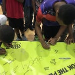 Students sign a pledge not use their smartphones while driving during a presentation at a youth camp at the Supreme Council of the House of Jacob.