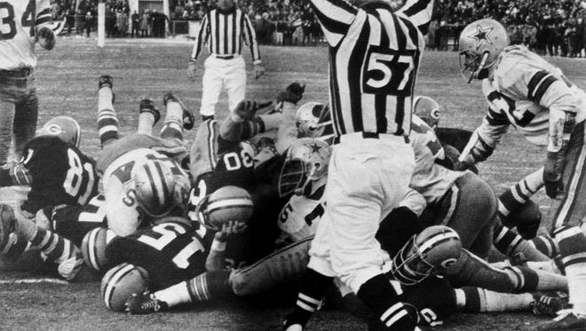 Packers quarterback Bart Starr (15) dives across the goal line with 13 seconds to go for the winning TD in the 21-17 triumph over the Cowboys in the NFL championship at Green Bay. Starr followed the block of Jerry Kramer (64) into the end zone.