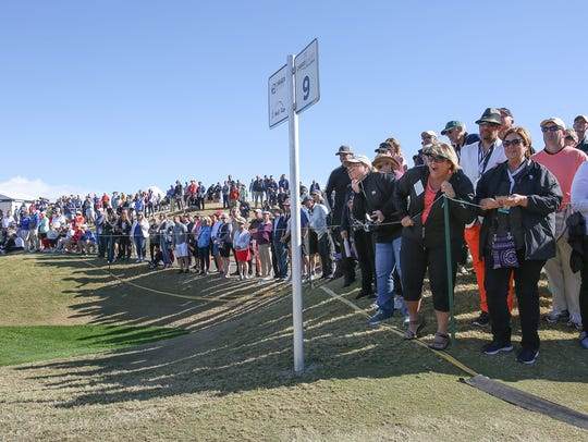 Fans watch the golf action on the 9th hole of the Stadium