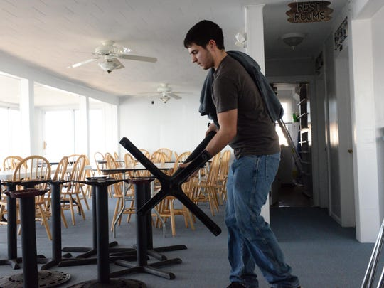 Dylan Gentile, 18, a student at Vineland High School, helps set up dining room tables and chairs in the Charlesworth Hotel & Restaurant in Fortescue in preparation of a New Year's Eve reopening.