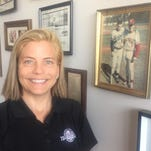 Jana Howser poses near an old photo of her father Dick Howser and then-Florida State assistant coach Chip Baker.