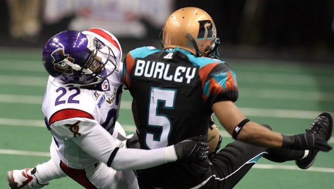 New Orleans VooDoo defender Keon Raymond (left) brings down Arizona Rattlers receiver Siaha Burley in Phoenix during a game on April 17, 2008.