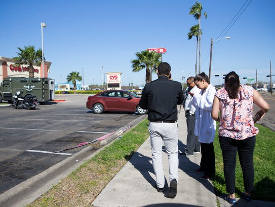 Employees of the CVS store on Alameda Street wait outside