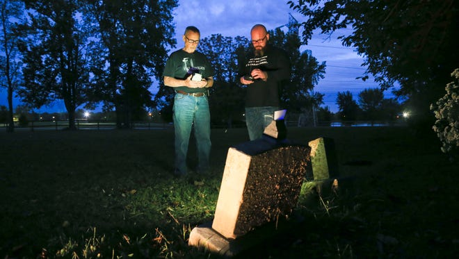 Paranormal investigators Mike Culwell, left, and Matthew Jackson conduct an investigation at a potter's field cemetery at the Sam Peden Community Park in New Albany earlier in October. Culwell is a retired detective from the New Albany Police Department. Both have experienced paranormal experiences from hearing voices to seeing apparitions during their investigations at places such as Waverly Hills and the old 'poor farm' in New Albany that's located near Sam Peden park.