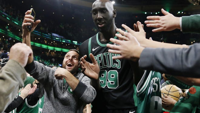 Celtics center Tacko Fall (center) comes off the court following an NBA basketball game against the Charlotte Hornets in Boston, Sunday, Dec. 22, 2019.