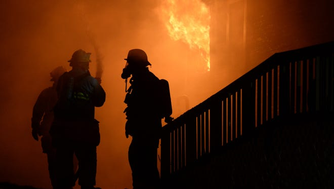 Firefighters work to extinguish a fire.