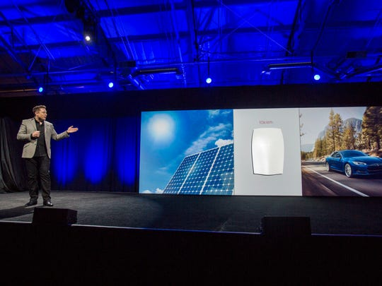 """Elon Musk, CEO of Tesla Motors Inc., unveils the company's new product called """"Powerwall"""" in Hawthorne, Calif., Thursday, April. 30, 2015. Musk is trying to steer his electric car company's battery technology into homes and businesses as part of an elaborate plan to reshape the power grid with millions of small power plants made of solar panels on roofs and batteries in garages. (AP Photo/Ringo H.W. Chiu)"""
