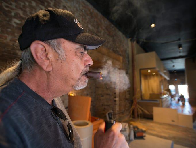 Owner David Sharruf lights up a cigar inside his Cigar