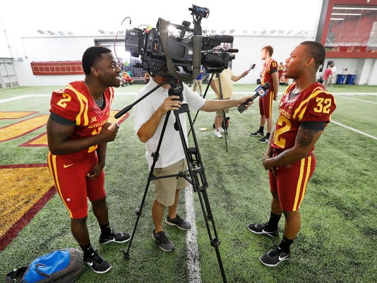 Iowa State running back Mike Warren, left, looks through a video camera as teammate running back David Montgomery, right, is interviewed during Iowa State's annual NCAA college  football media day, Thursday, Aug. 3, 2017, in Ames, Iowa. (AP Photo/Charlie Neibergall)
