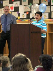 Jose Barrios sixth-grade elementary student Dace Begay speaks in front of his school on Friday afternoon with principal Travis Yurcic looking on.