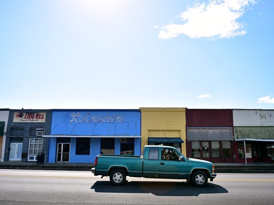A truck drives past a cluster of closed businesses in downtown Macon.