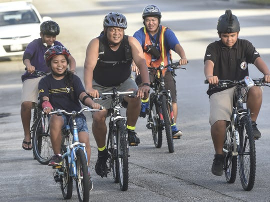 Paul Lujan, center, rides with his daughter, P.J. Lujan,