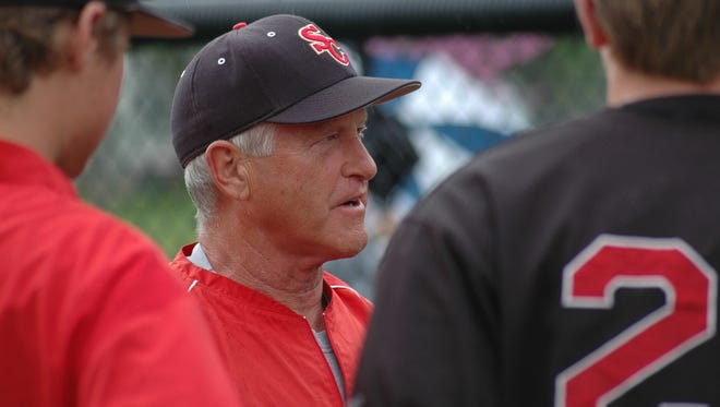 Longtime Simpson College pitching coach Joe Blake huddles with players during an Iowa Conference Tournament game in 2013.