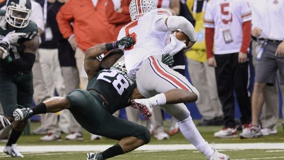 MSU's Denicos Allen makes a fourth-down stop of Ohio State quarterback Braxton Miller late in MSU's  Big Ten Championship game win in December of 2013. It is one of the critical moments in MSU football history.