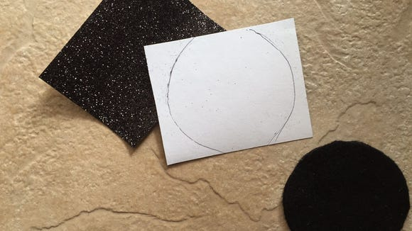 Turn the black glitter paper over and trace the black