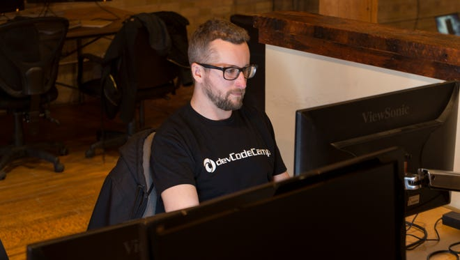 Joel Corey, a veteran of the war in Afghanistan, works at devCodeCamp in Milwaukee. Corey is among veterans taking a boot camp in computer coding using GI Bill educational benefits.