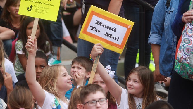 Elementary students hold up signs for the 25th annual Read to Me March Around the Courthouse Friday, April 15, on the steps of Tom Green County Courthouse.