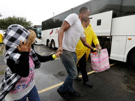 A family is helped to a bus as they are evacuated as