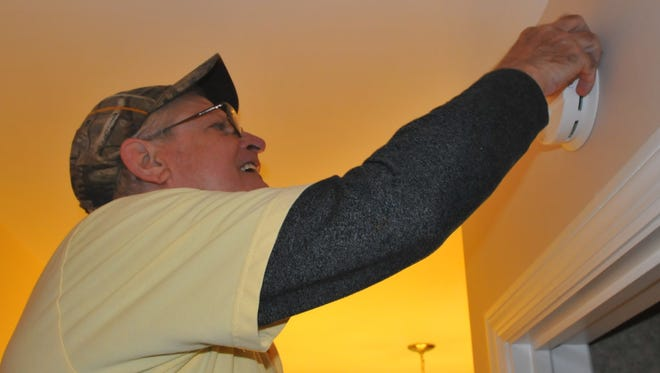 Les Robinson installs a smoke detector in the home of Deena and Ray Armstrong as part of the American Red Cross' Home Fire Campaign.