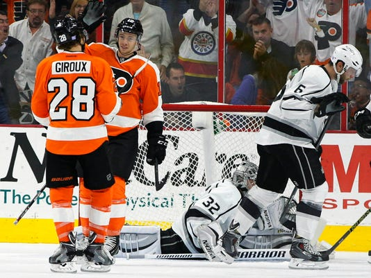 Philadelphia Flyers' Michael Raffl, center left, celebrates his goal with Claude Giroux, left, as Los Angeles Kings' Jonathan Quick, center right, and Jake Muzzin, right, react during the first period of a hockey game, Tuesday, Oct. 28, 2014, in Philadelphia. (AP Photo/Chris Szagola)