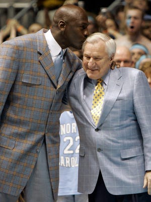 Former North Carolina player Michael Jordan, left, gives his former coach Dean Smith a kiss during halftime of a college basketball game between North Carolina and Wake Forest on Feb. 10, 2007. The 1982 and 1957 championship teams were recognized during a halftime ceremony. Jordan was a member of the 1982 team. Smith died on Saturday.