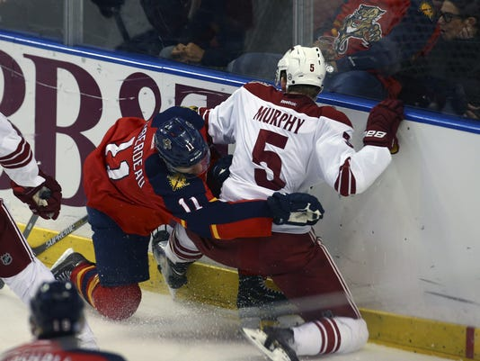 Florida Panthers' Jonathan Huberdeau (11) and Arizona Coyotes' Connor Murphy (5) fight for the puck during the second period of an NHL hockey game in Sunrise, Fla., Thursday, Oct. 30, 2014. (AP Photo/J Pat Carter)