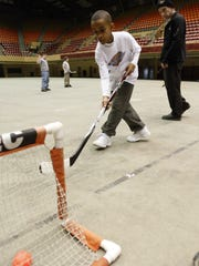 Frank Meeink, right, watches as Jalen Jones, 9, puts one in the net on Jan. 24, 2008. Meeink is a former skinhead leader from south Philadelphia who now goes around the country telling his story and speaking out against hate groups and racial intolerance. He was doing marketing for the Iowa Stars and helped start the Stars' Harmony through Hockey program, which brought together disadvantaged children from different backgrounds and taught them life lessons as they learned the sport of hockey.